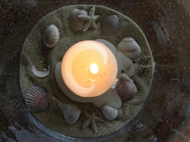 Candle in sand above