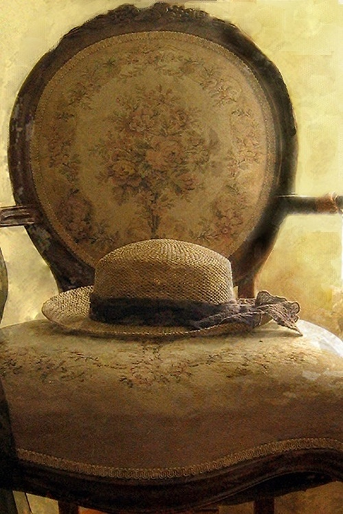Straw hat in tapestry chair